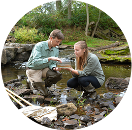 Professor and student kneeling near stream