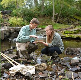 Professor and student kneeling near stream