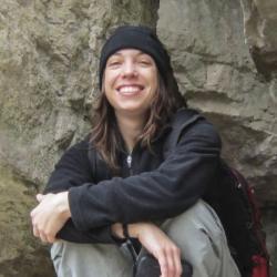 Alumni Katie Costanzo crouching by rocks