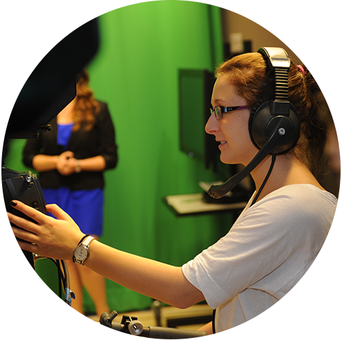 A student does camera work in front of a green screen