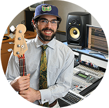 Music student holding guitar in recording lab