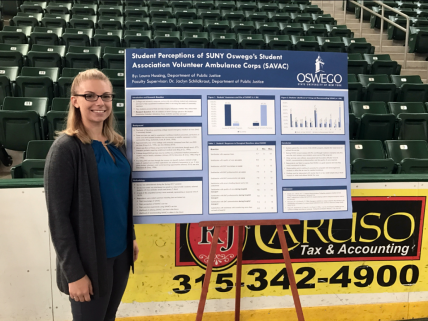 Laura Hussing stands beside research poster in the arena