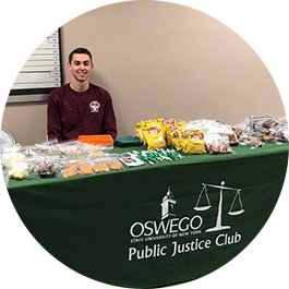 Male student sits at Bake Sale table