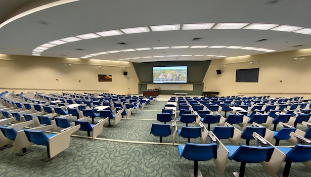 Photo of the back of the classroom from the center. Including the screen/podium/seats.