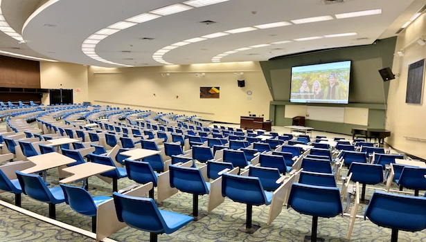 Photo of the back of the room from the side of the classroom. Showing seats, podium, and projector.