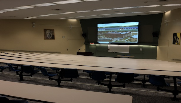 This photo shows the back of the classroom with all of the seats and the large projector screen.