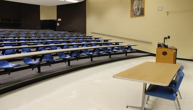 This is a side view of the classroom with the seats, professor table and side of the podium.