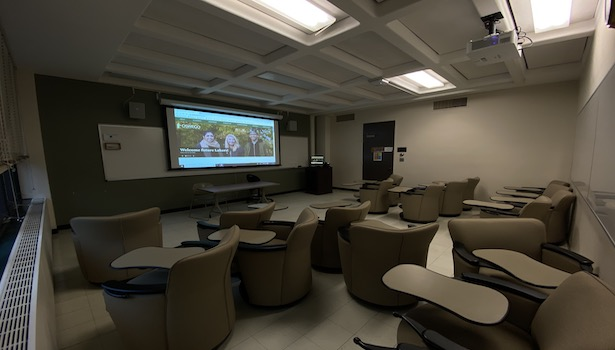 Photo shows the front of the classroom from the back left side. Including student seats, projector screen and podium.