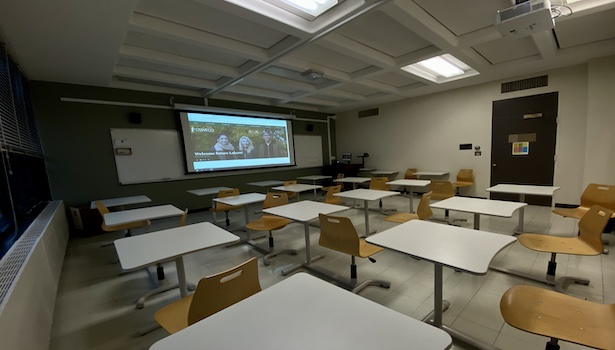 Photo shows the front of the room from the back left side. Including student chairs, podium and projector.