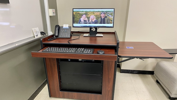 Photo shows the podium in this classroom including the PC and the handicapped side table.