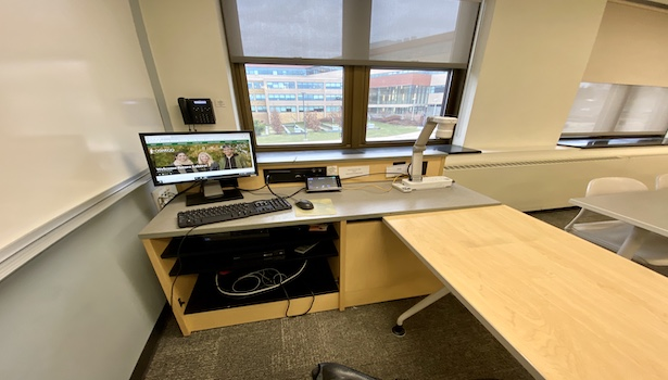 Photo shows the podium in the classroom including the PC, touch panel, document camera and phone.