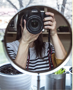 Photo of a person taking a photograph of themself in a mirror