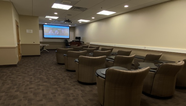 Photo of the front of the classroom from the left side of the room. Showing student chairs and projector screen.