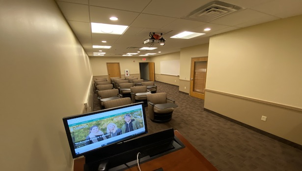 Photo of the classroom from the front podium. Showing the projector and student chairs.