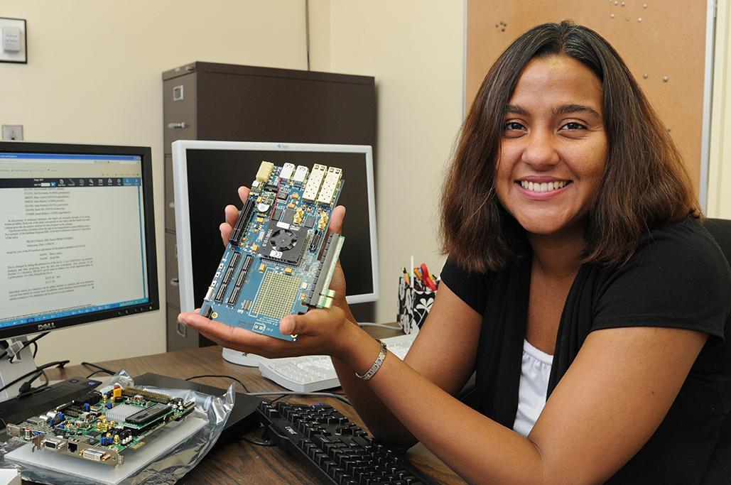 Professor Marianne Hromalik holding the XPRESS FX Virtex-4 FPGA board for development