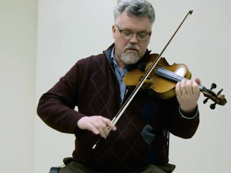 Faculty member David Deacon playing fiddle