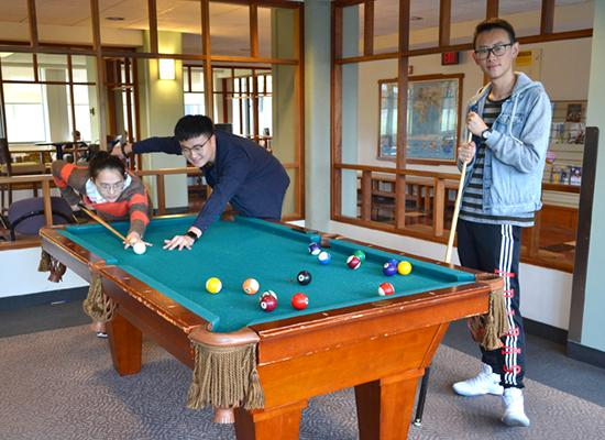 Student play pool in a Hart Hall lounge.