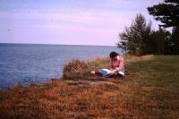 student studying by Lake Ontario