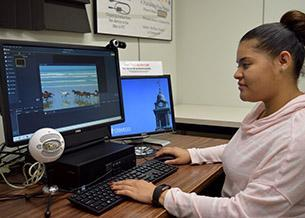 Student working in a multimedia creation room in the library.