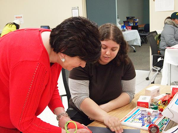 A librarian assisting someone with a 3D pen.