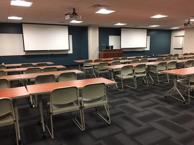 The Speakers' Corner Classroom, showing its two projection screens, and four rows of tables with chair at them.