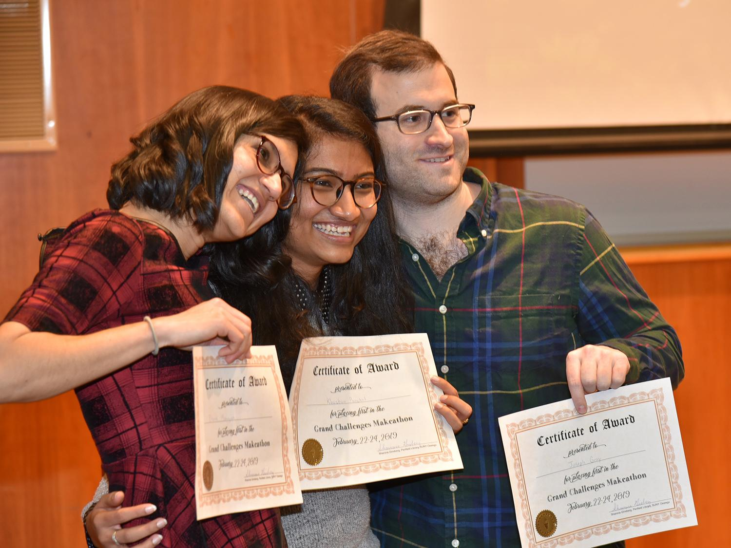 Three students with certificates after their app proposal won Grand Challenges Makeathon