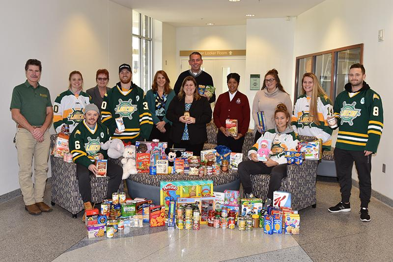 Hockey teams with collected toys and other donations