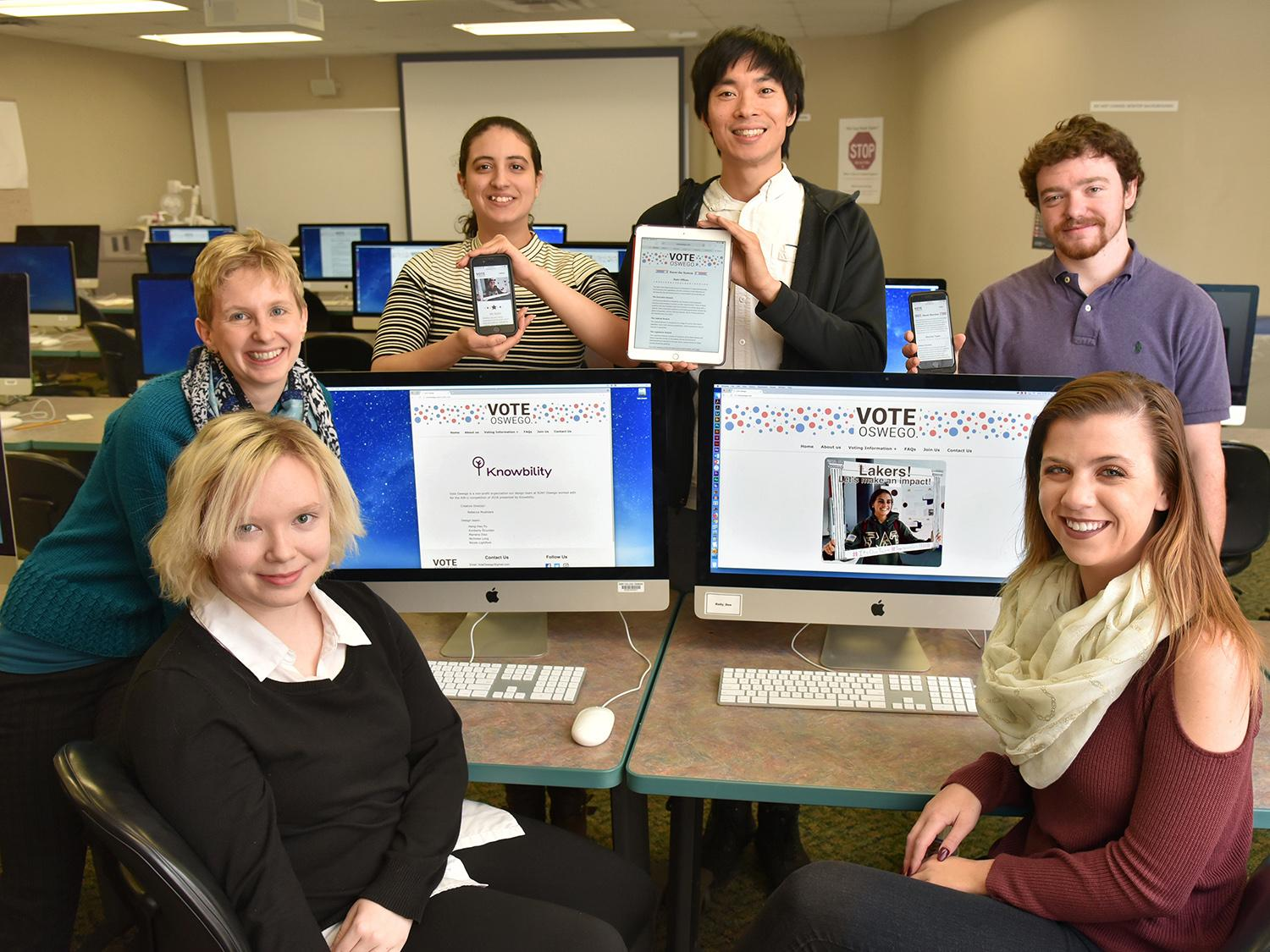Students and faculty show off the Vote Oswego site they designed which won a national accessibility award