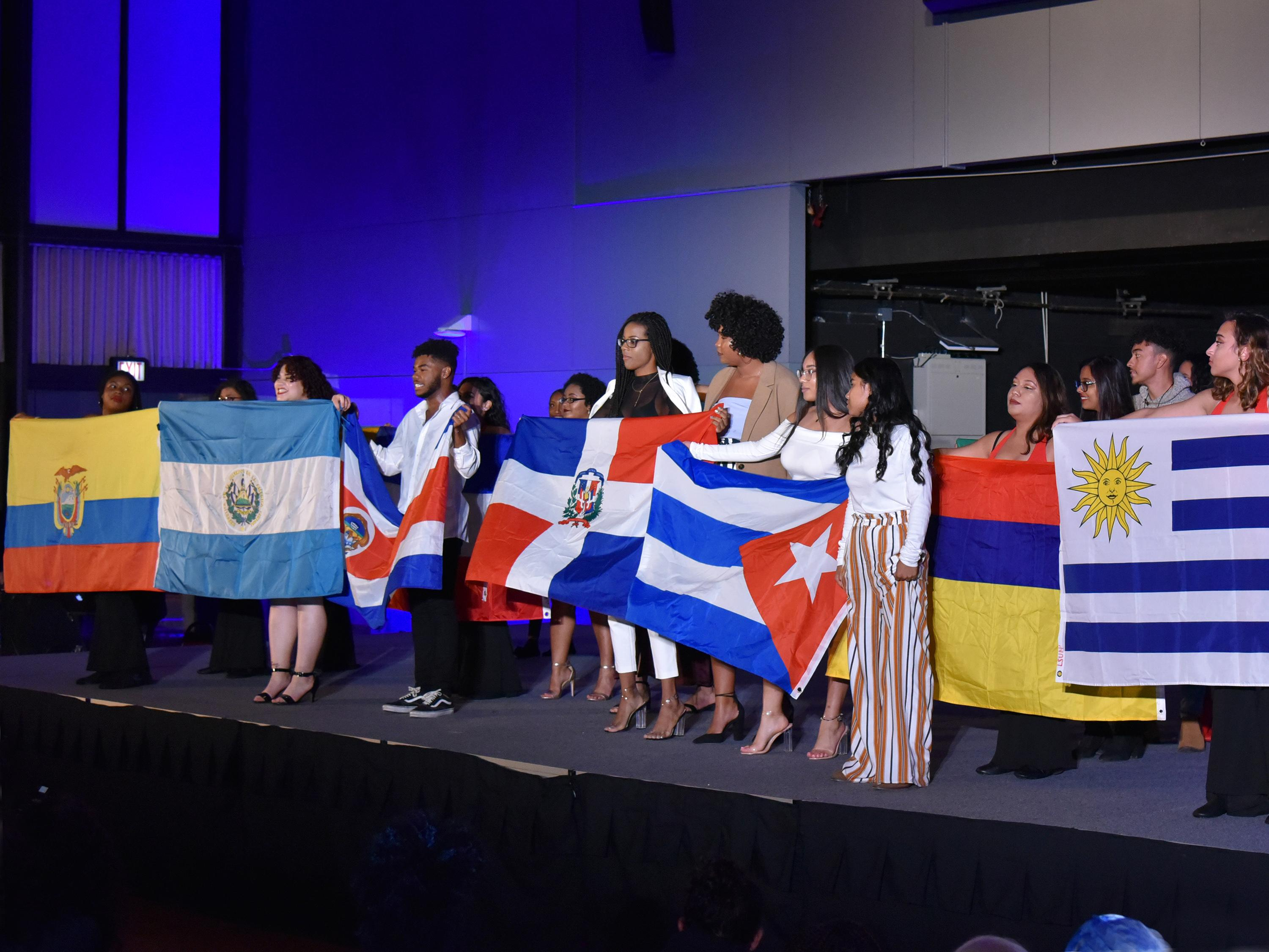 Students hold flags of many nations at 2018 ALANA Fashion Show