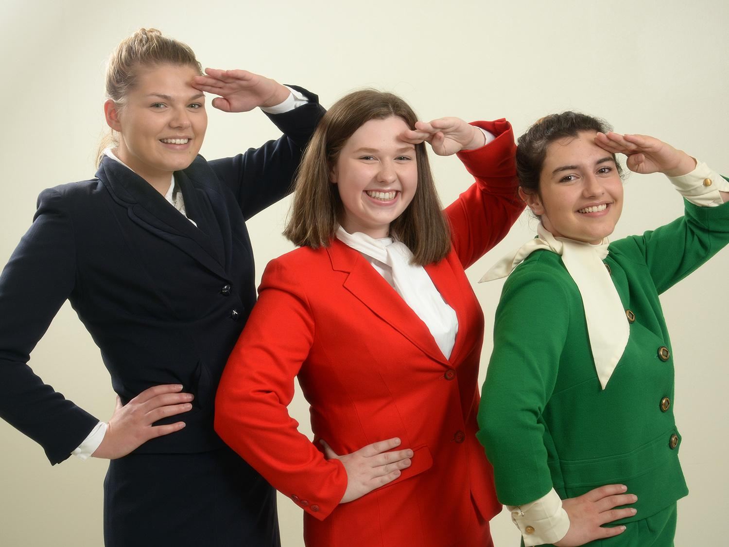 3 actresses dressed as stewardesses salute the camera