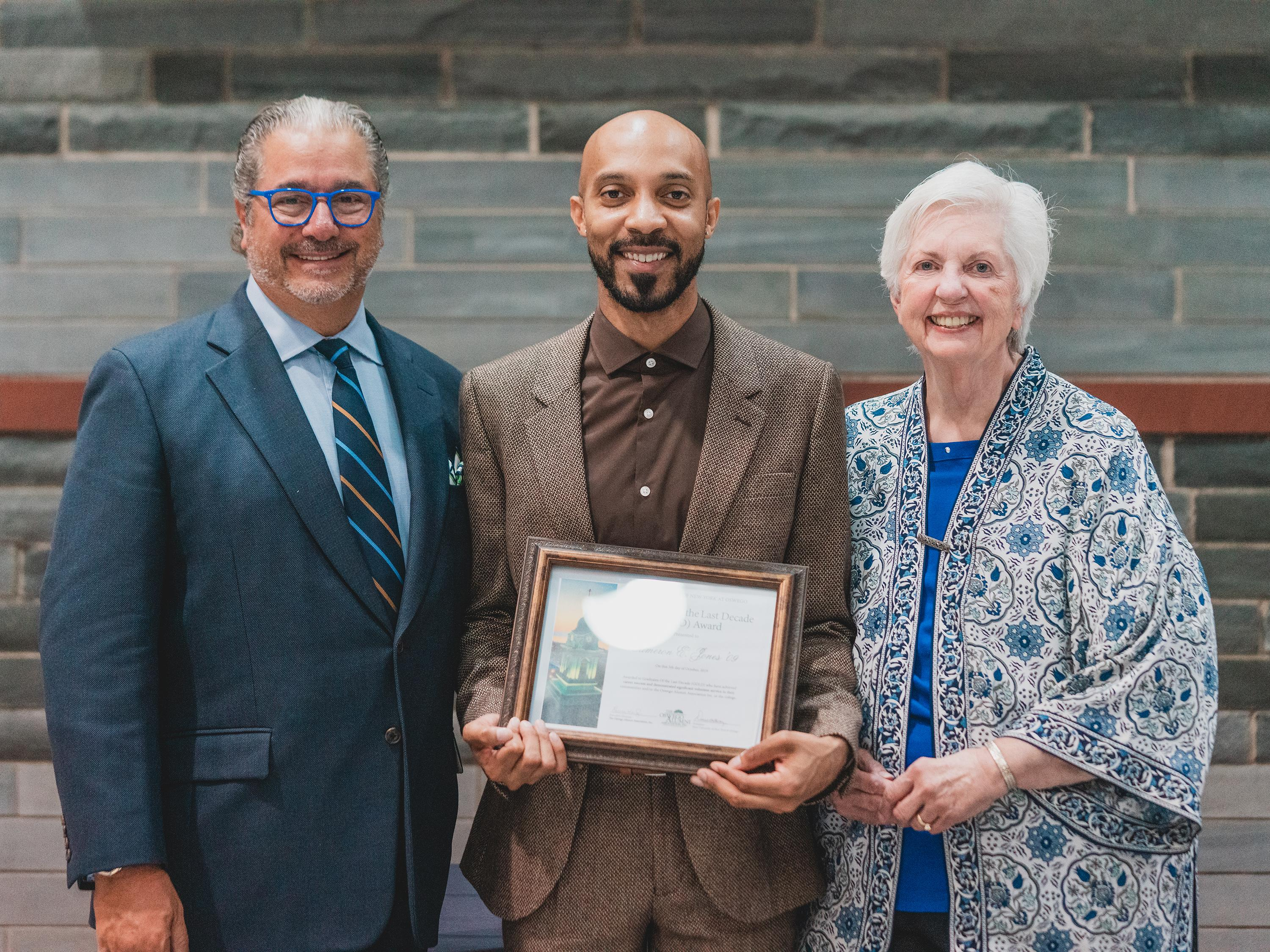 Three-time Emmy Award-winning producer Cameron Jones (center) of SUNY Oswego's Class of 2009 was honored recently by the Oswego Alumni Association with a Graduate Of the Last Decade Alumni Award