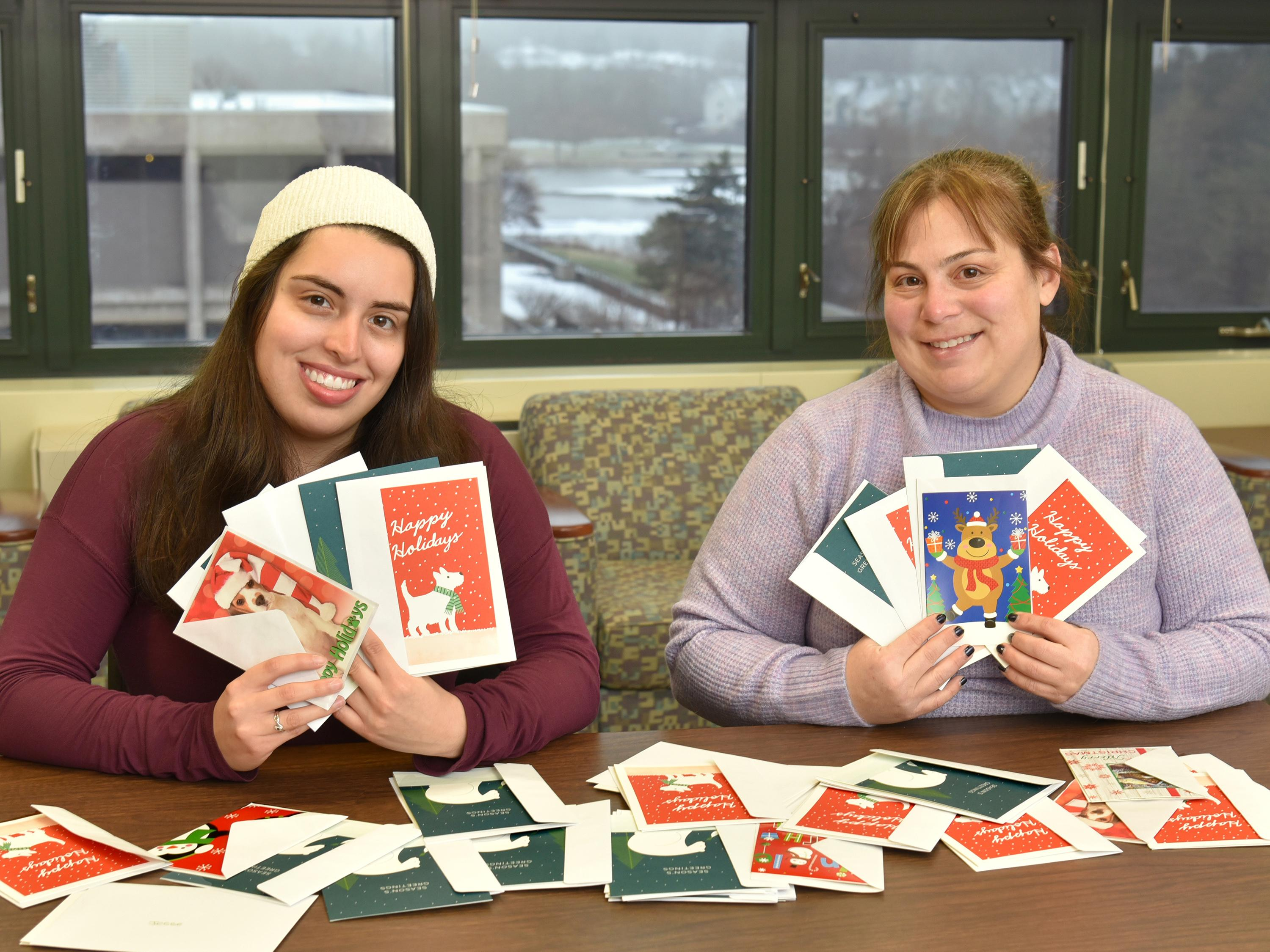 Sarah Gamarra and Jaclyn Schildkraut showing some of the donated holiday cards