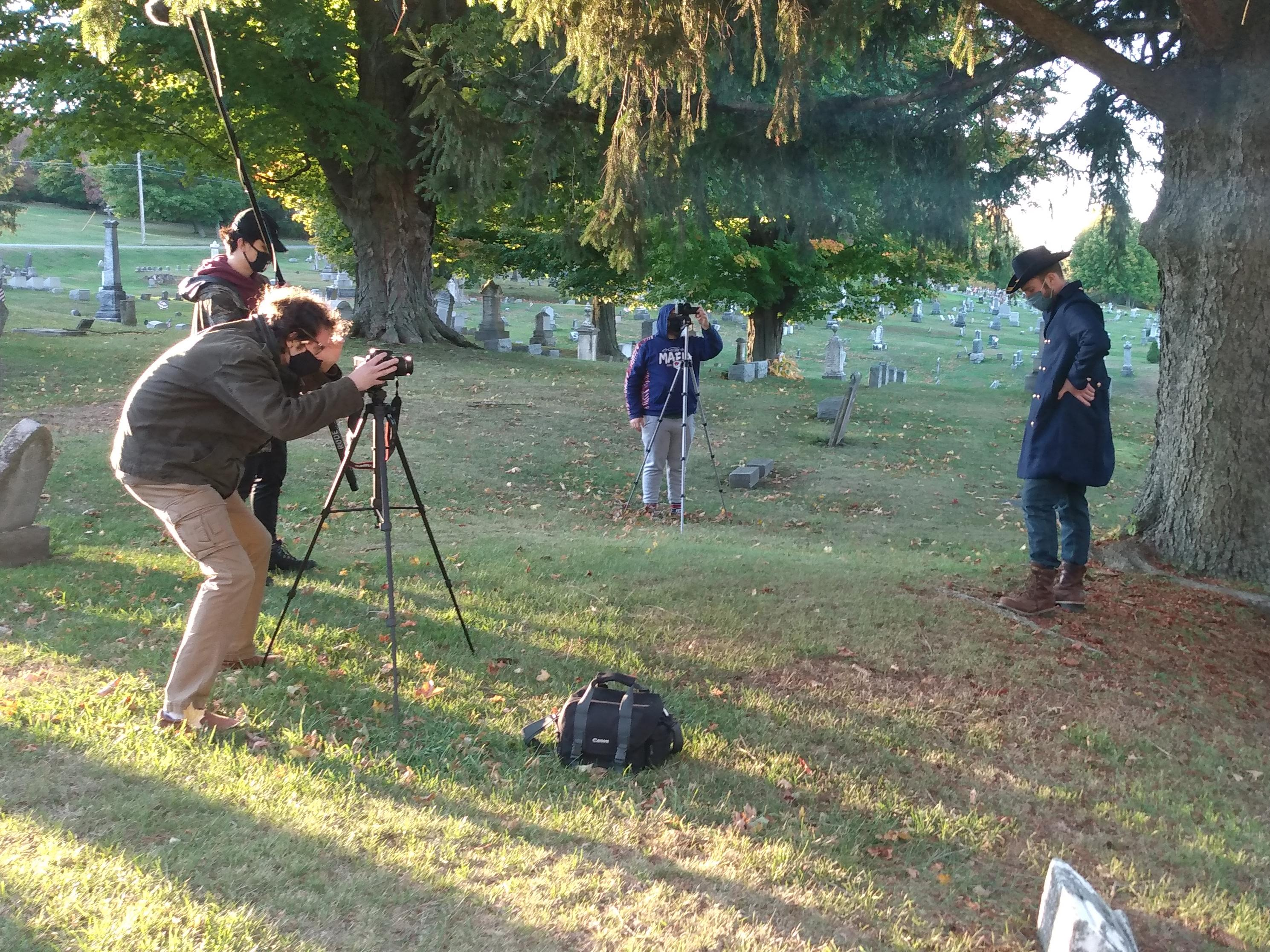 Students acting and filming cemetery storytelling