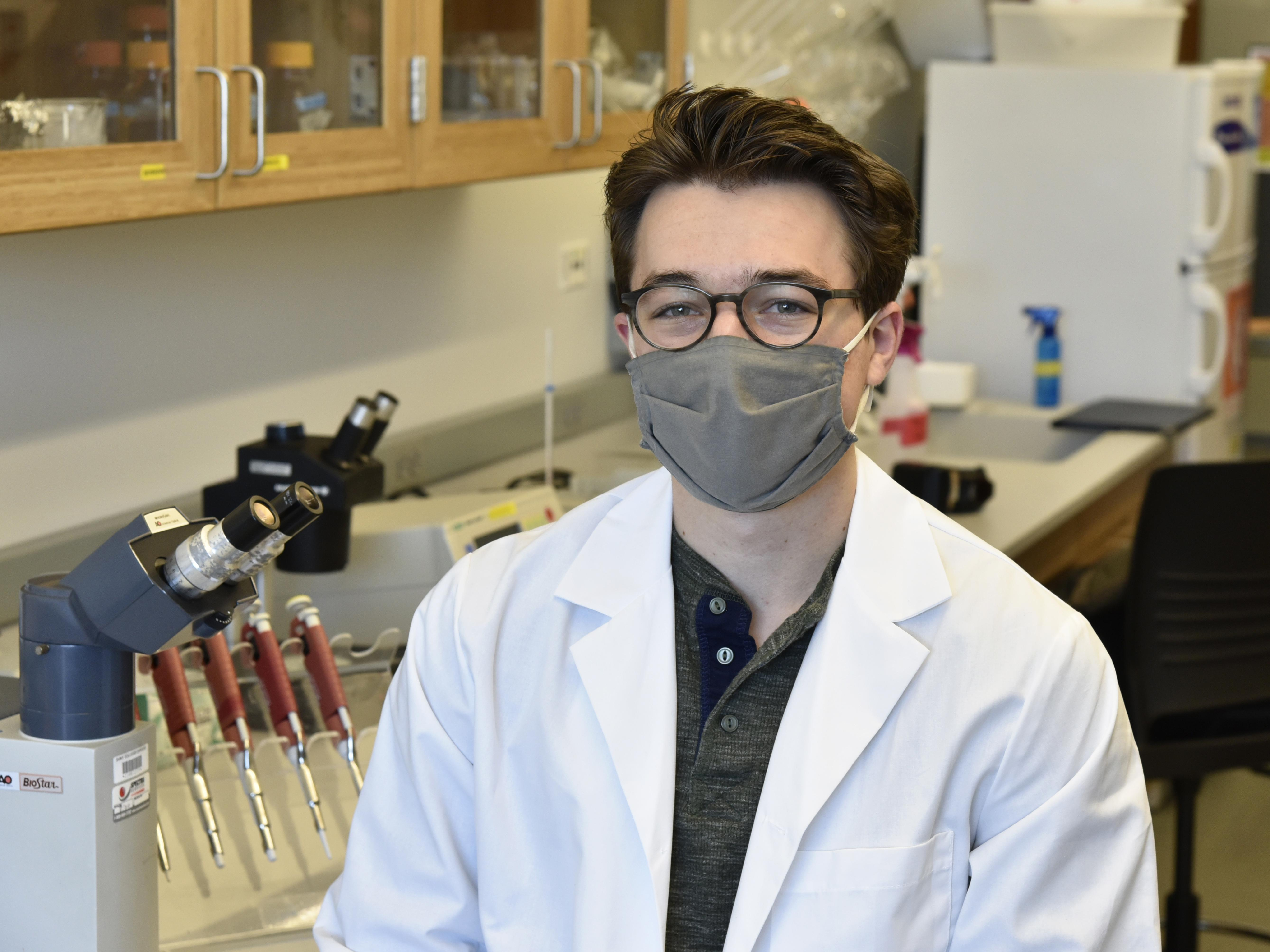 Christian DiBiase sits in a Shineman Center lab surrounded by research equipment