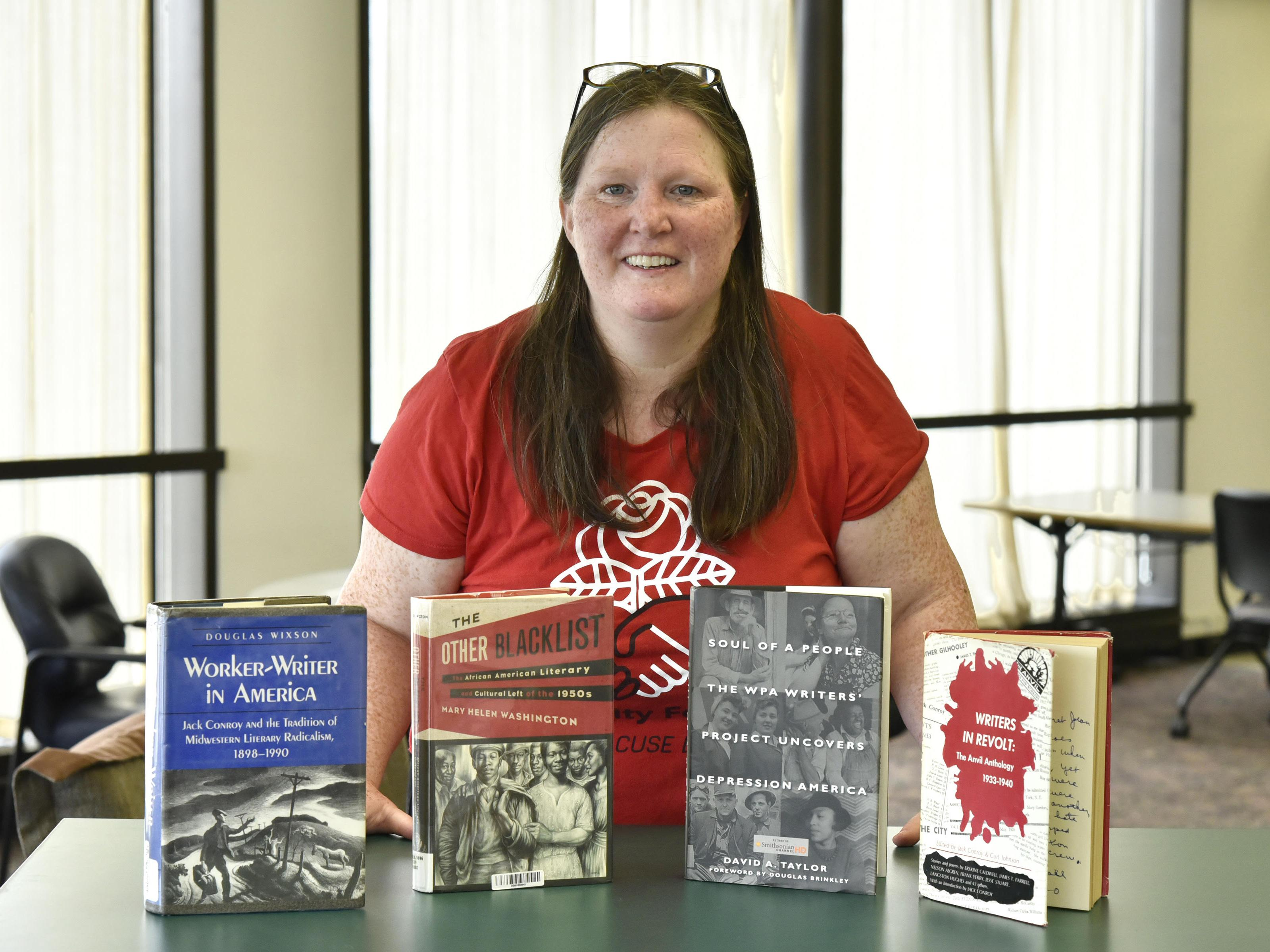 Maureen Curtin with books in Penfield Library