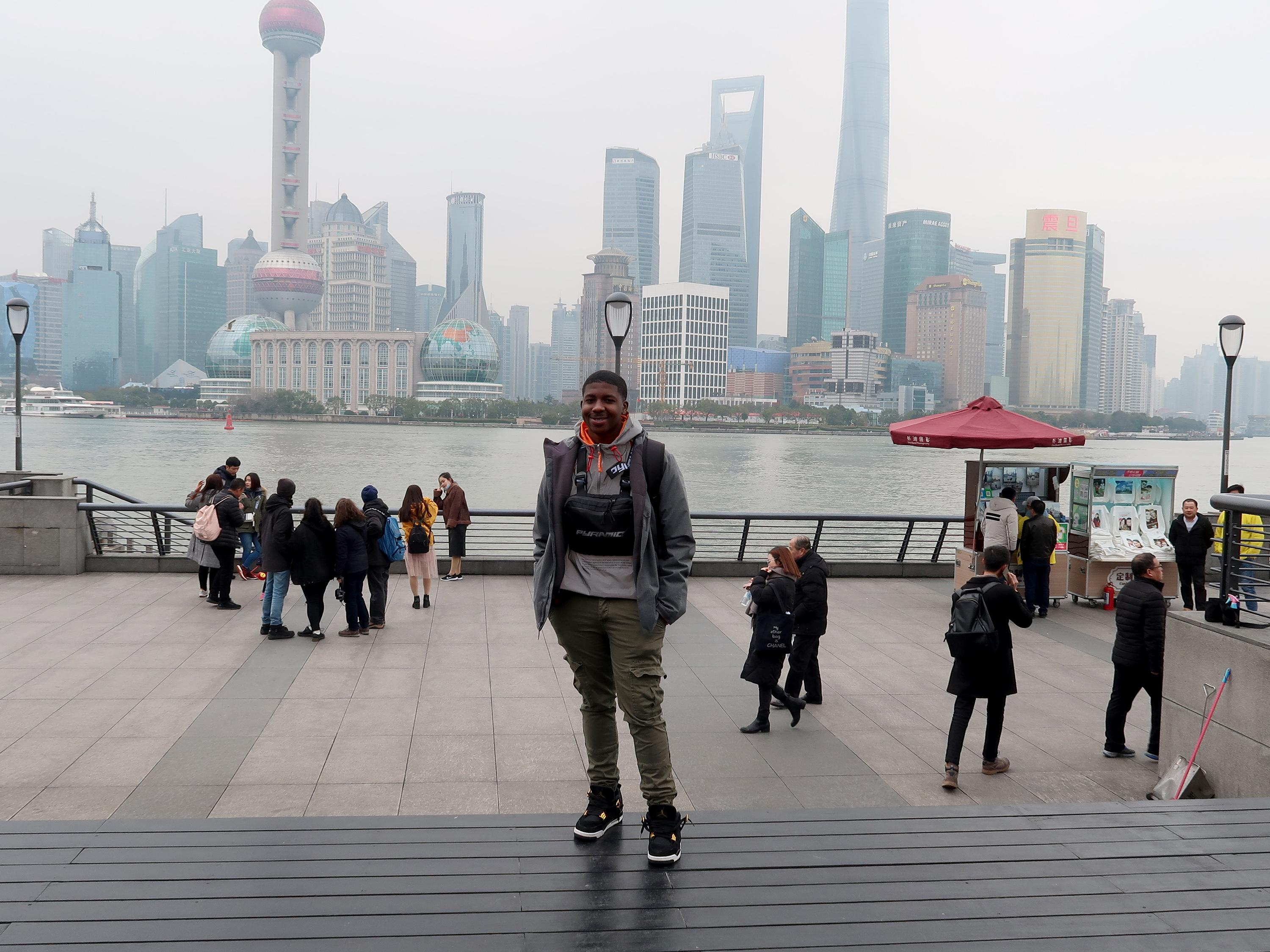 Diandre Coote-Anderson, senior finance major who studied abroad in Shanghai, China, stands in front of a modern cityscape