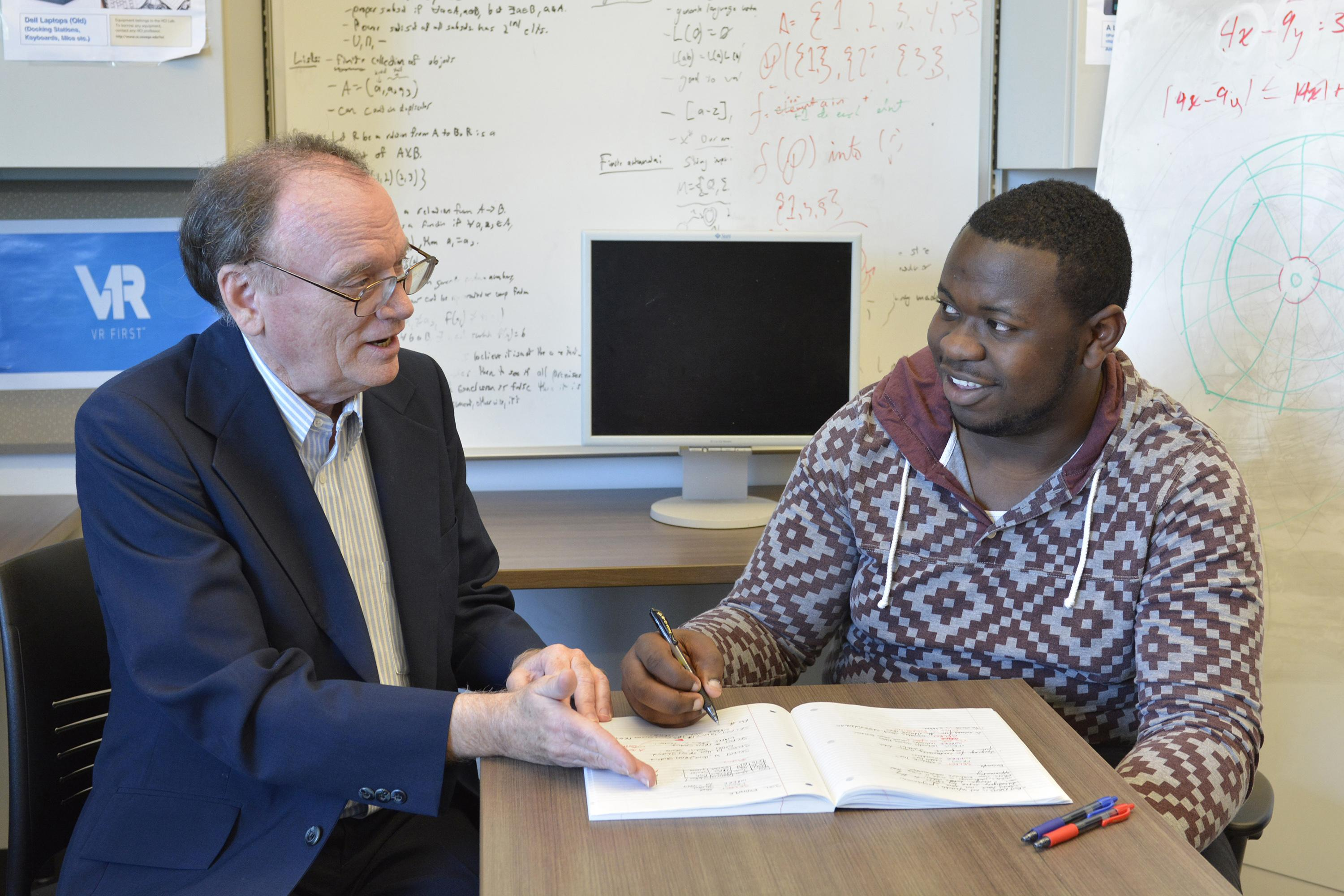 Faculty member David Vampola speaks with student Kingsley Ibezim