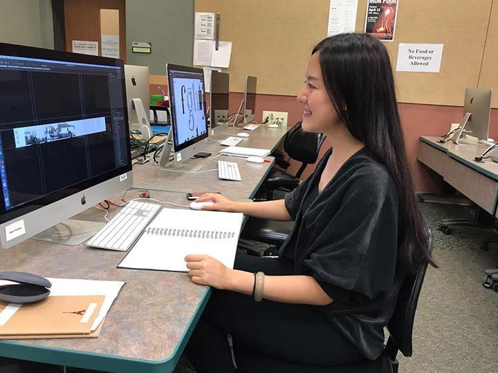 Master's in art student Jingyuan Duan works on her art using a computer