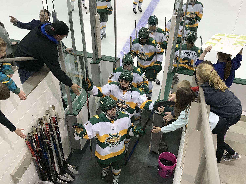 Women's hockey players high-five fans