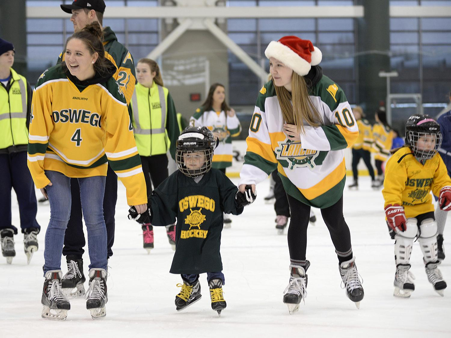Laker women's hockey players skating with children