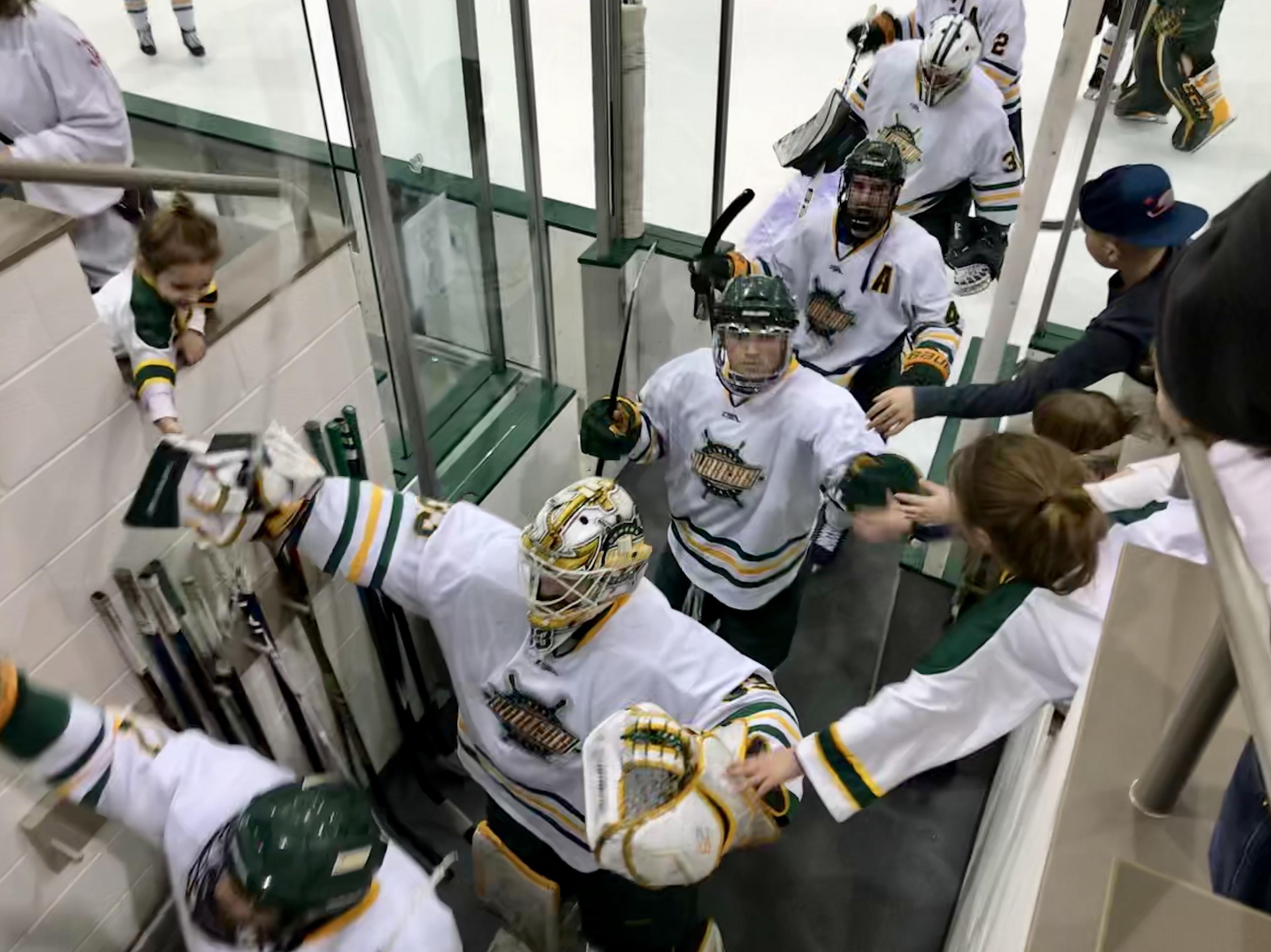 Men's hockey team high fives fans