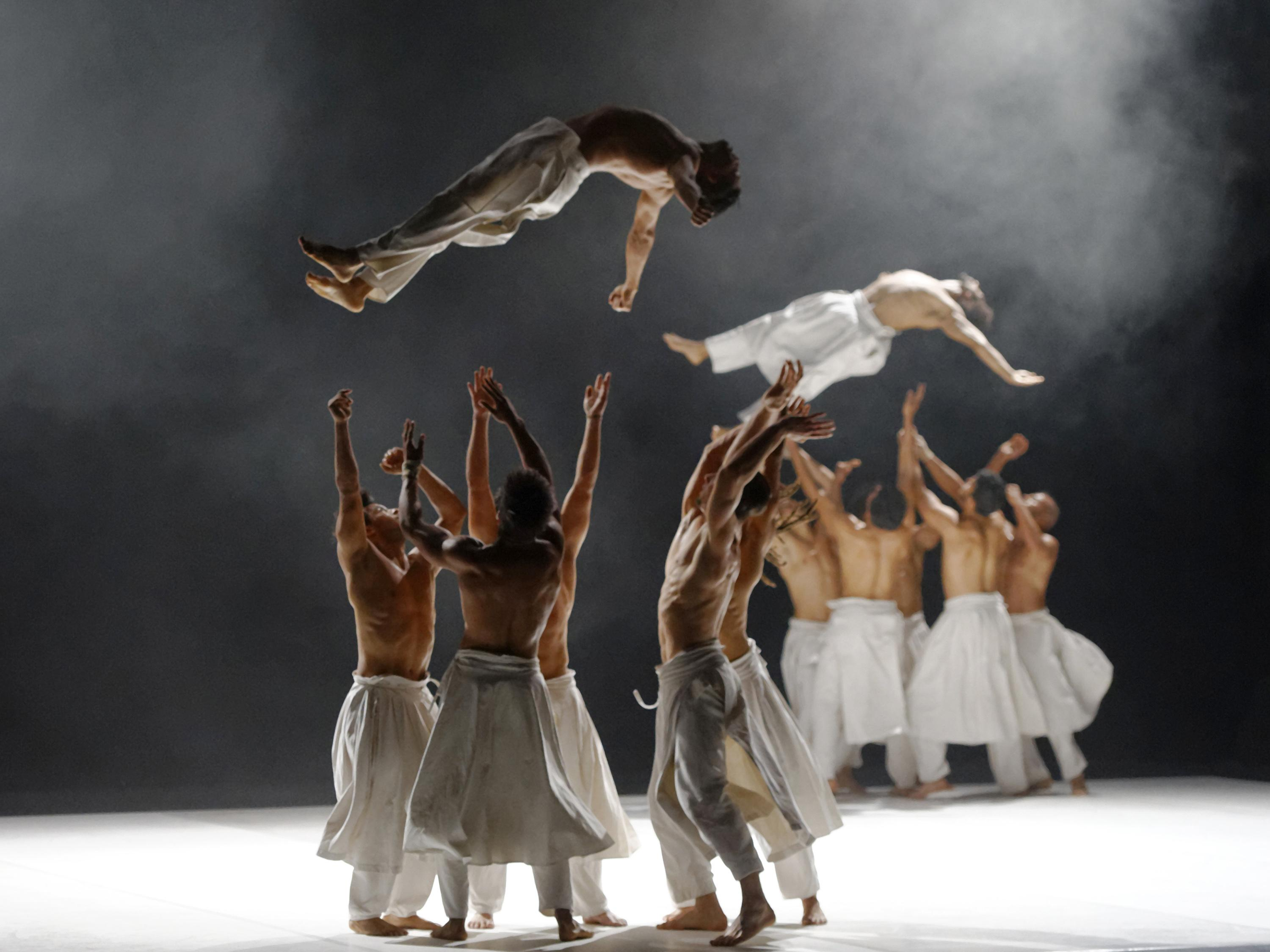 Dancers soar in the air as groups of fellow troupe member wait to catch them