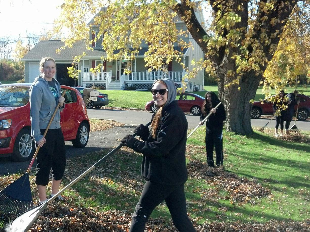 Student-athletes collecting leaves in a front yard