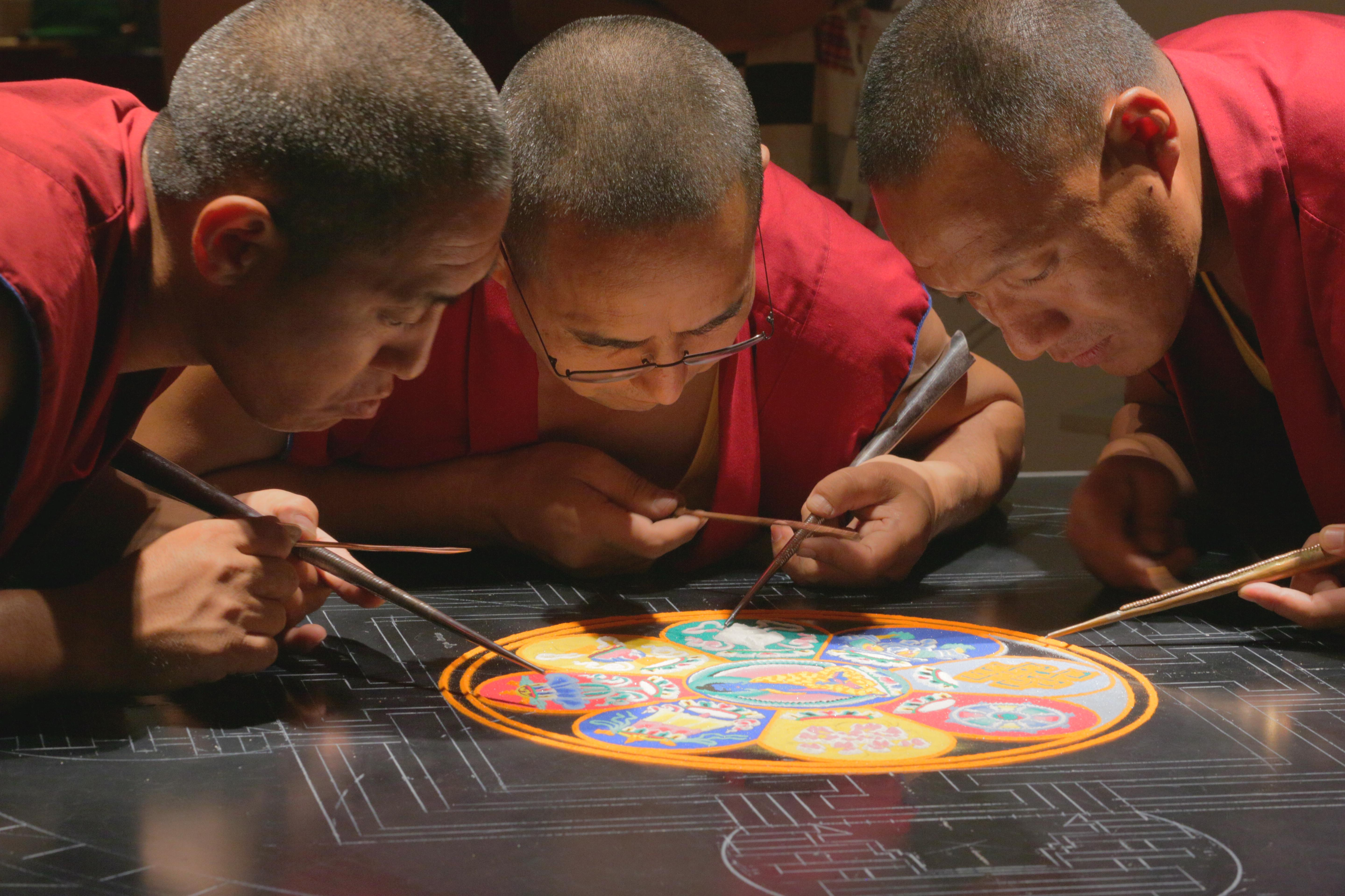 Monks work on creating mandala, beautiful sand art