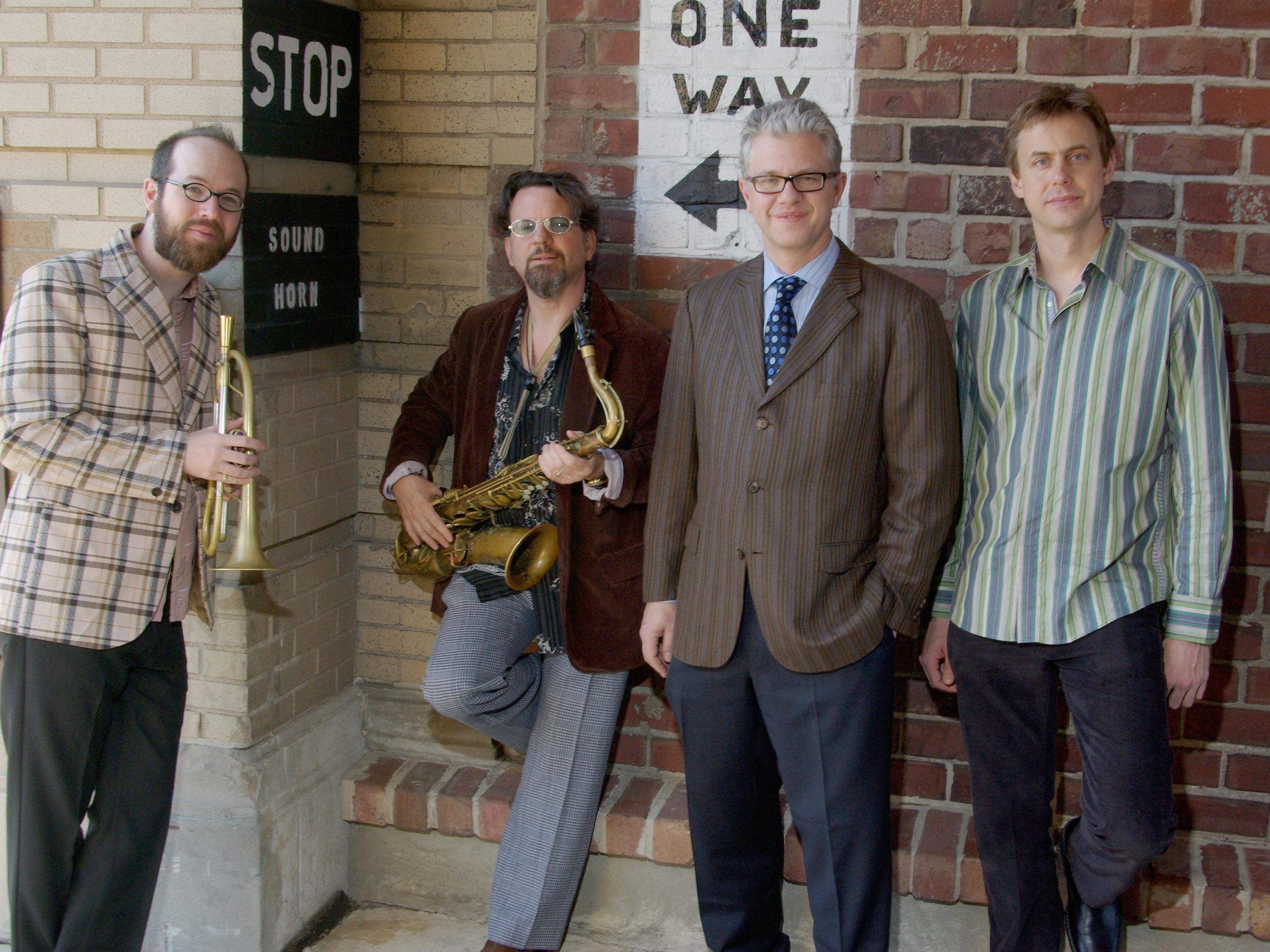 Matt Wilson Quartet standing against a wall, two of them holding horns