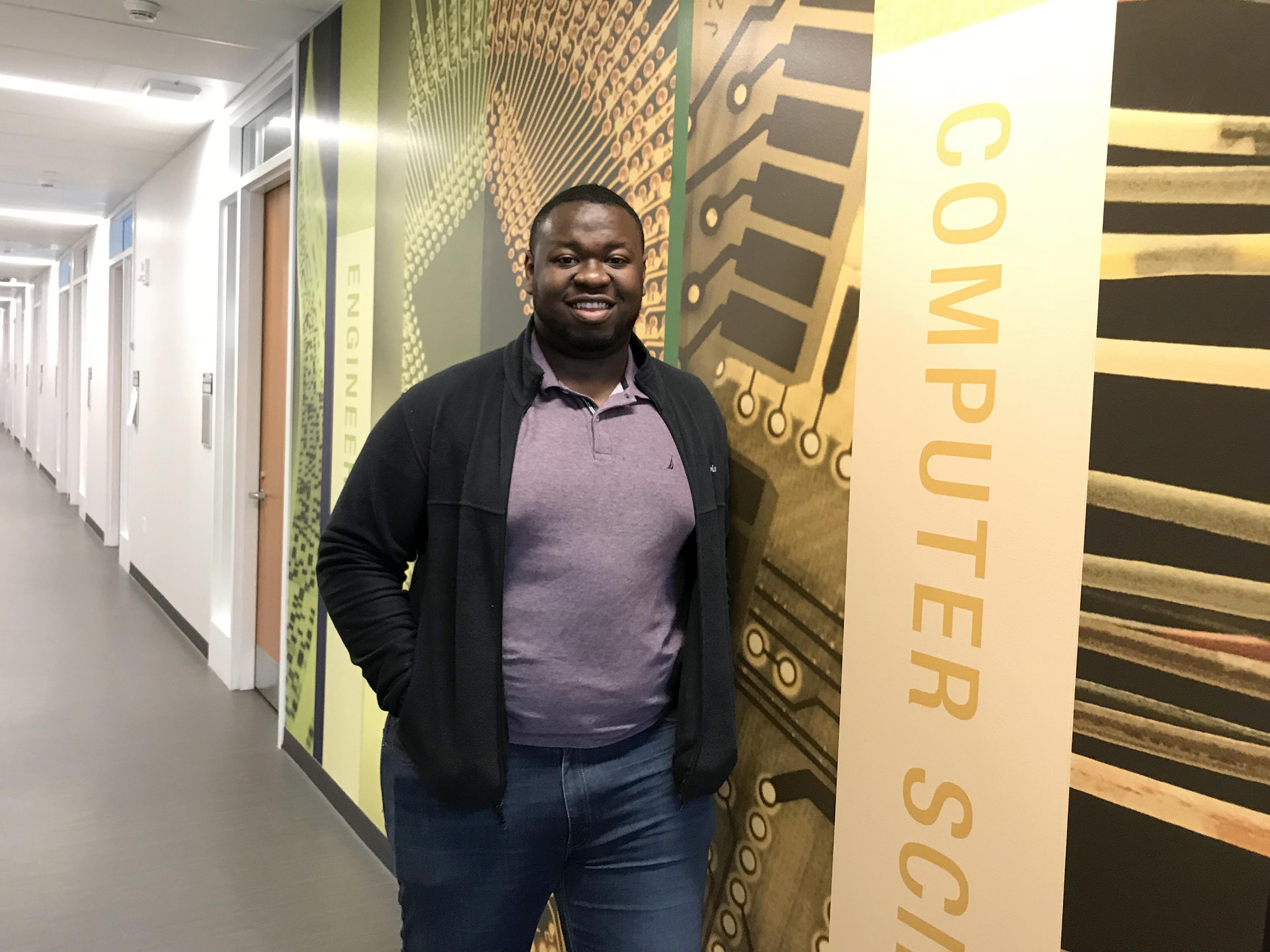 Kingsley Ibezim in front of a mural on computer science and other fields in the Shineman Center