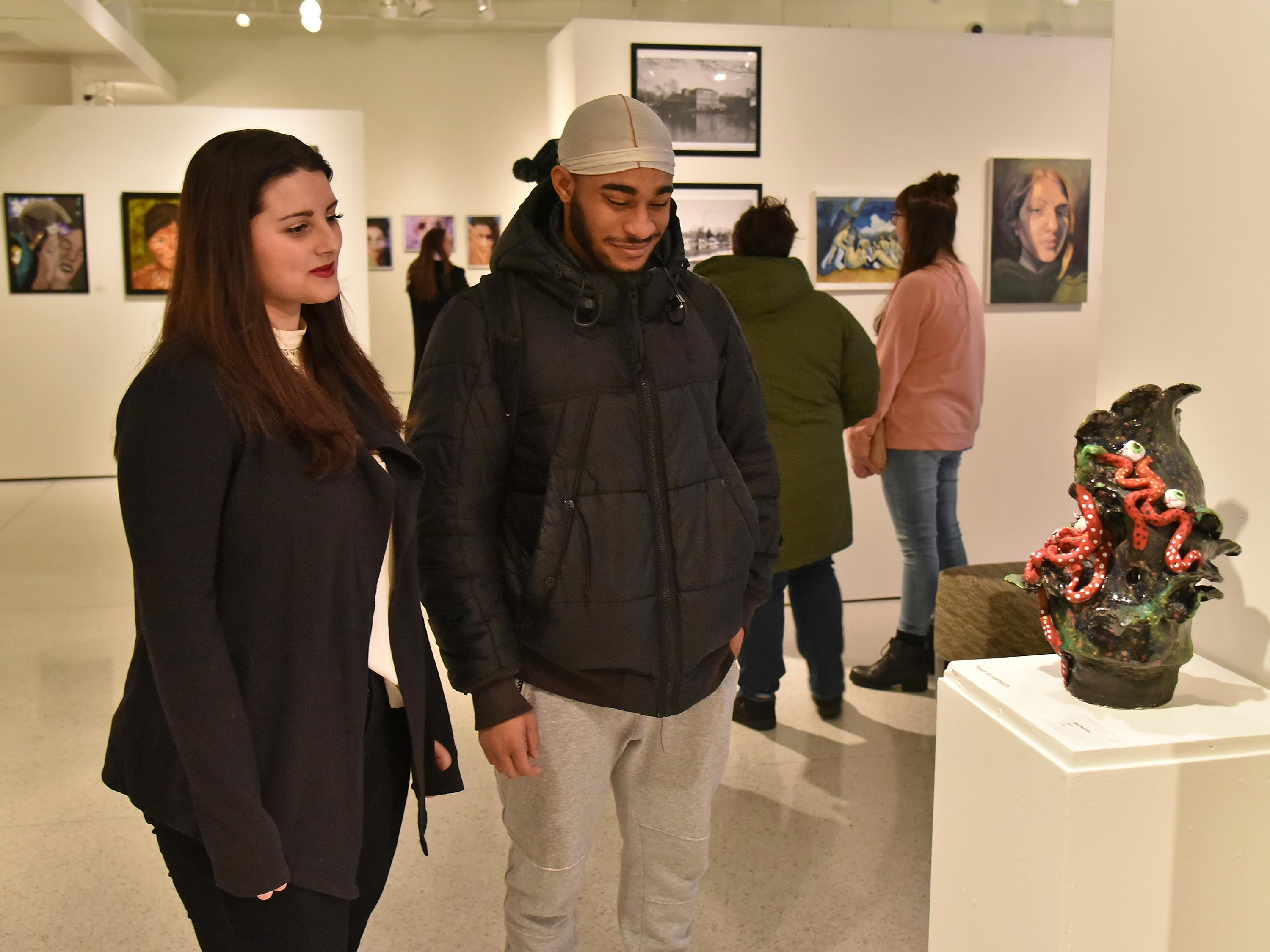 Shea McCarthy looks at her sculpture during Juried Student Exhibition