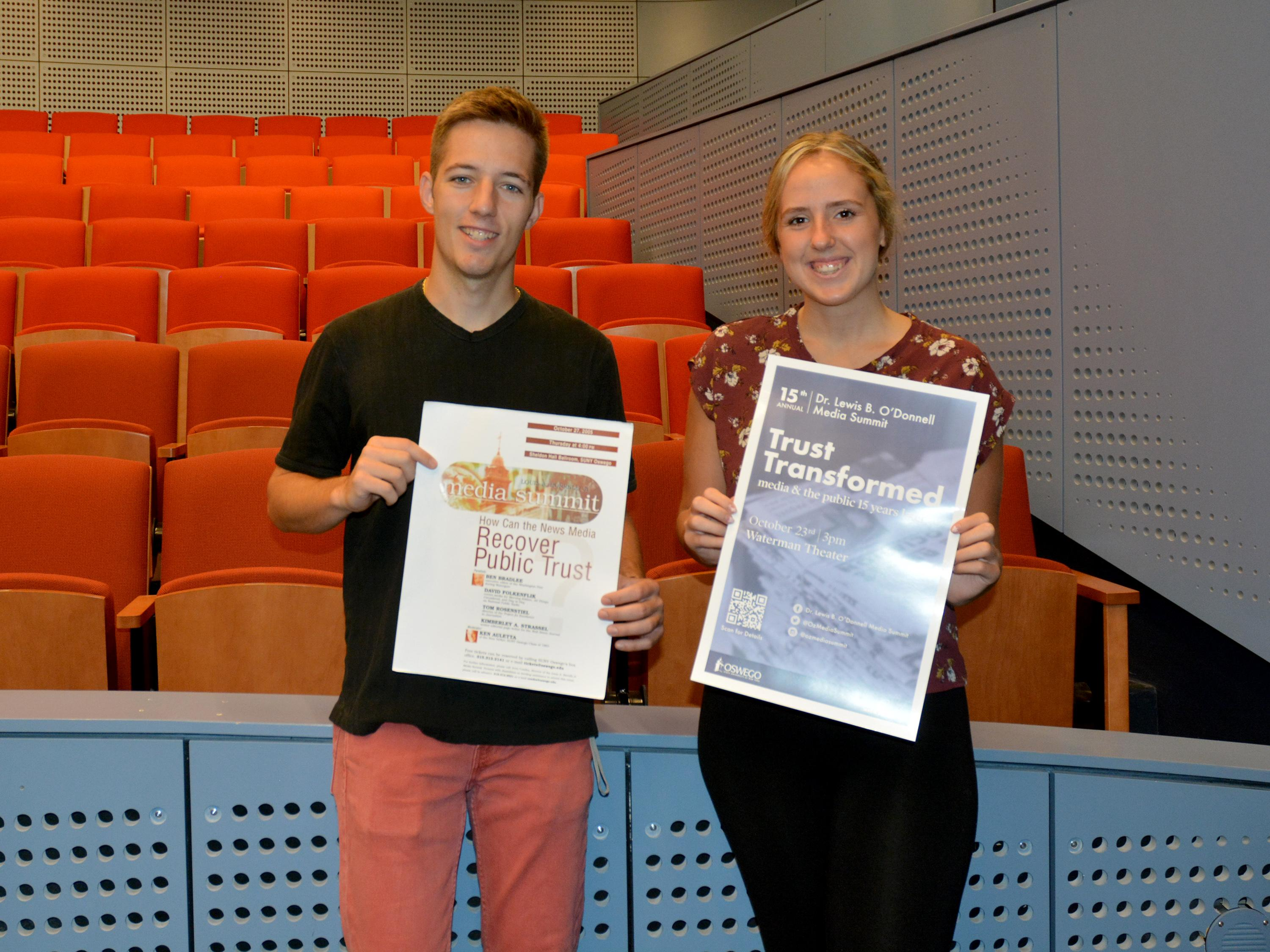 Josh Holfoth and Tori Kammer holding posters from the first media summit in 2005 and the 2019 edition
