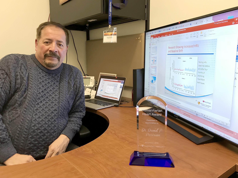 David Parisian with award and screen with data