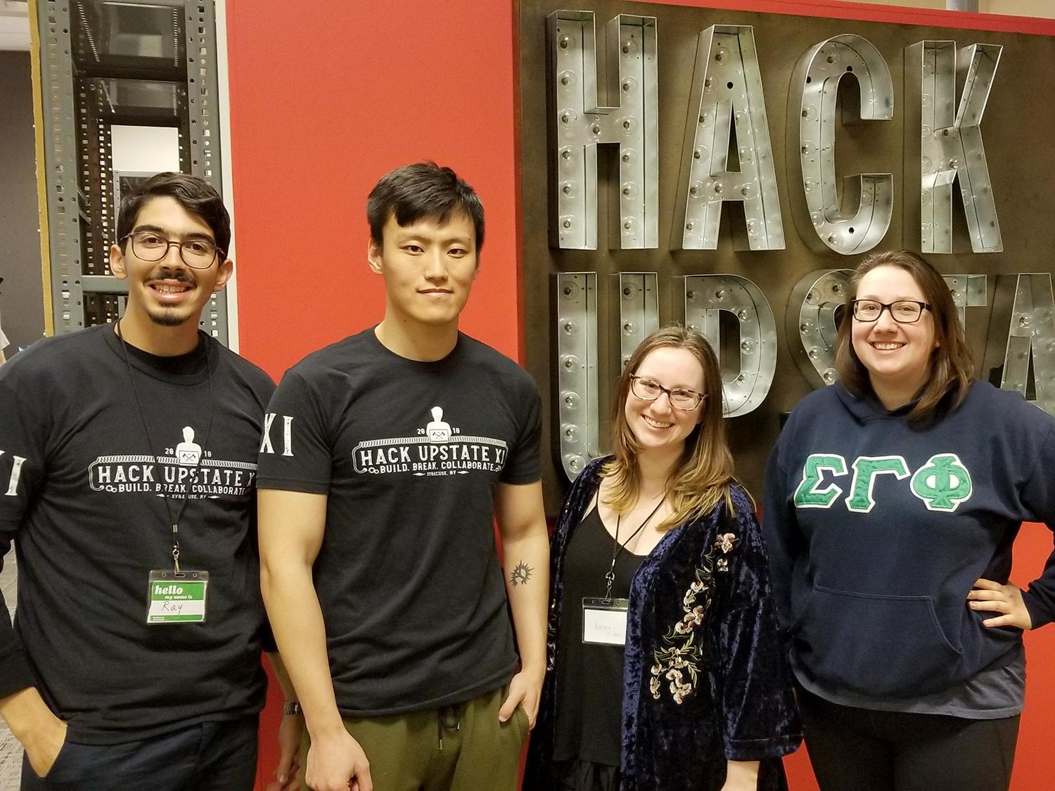 Student stand in front of the Hack Upstate sign